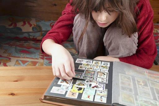 Девочка смотрит альбом с почтовыми марками | Hobby Keeper Articles